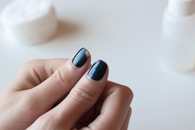 Ancienne manucure bleu foncé. vernis à ongles minable. mains de femme sur tableau blanc. spa.