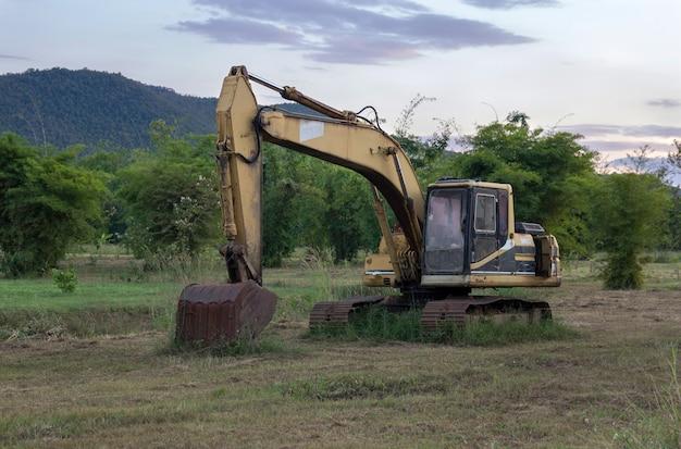 Ancienne pelle rétrocaveuse sur chantier dans les champs verdoyants avec coucher de soleil
