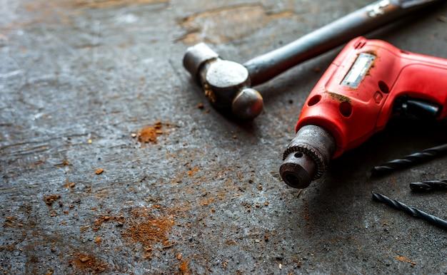 Ancienne perceuse sans fil et marteau de fer sur bois