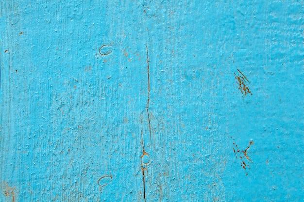 Ancienne planche de bois minable, peinte en bleu clair.