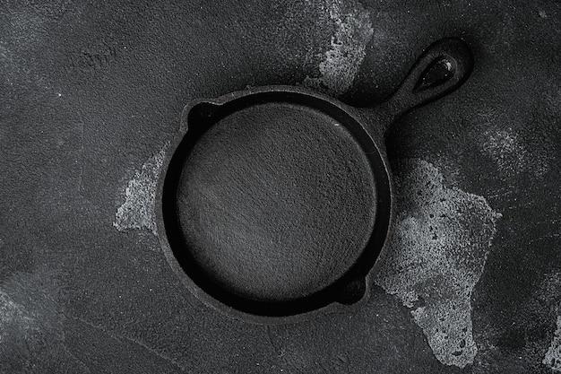 Ancienne poêle à frire vide utilisée avec espace de copie pour le texte ou la nourriture avec espace de copie pour le texte ou la nourriture, vue de dessus à plat, sur fond de table en pierre noire noire