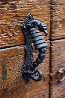 Ancienne poignée de porte en métal italien sur porte en bois marron.