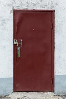 Ancienne porte en fer peint en marron avec serrures en métal. fermer. verticale.
