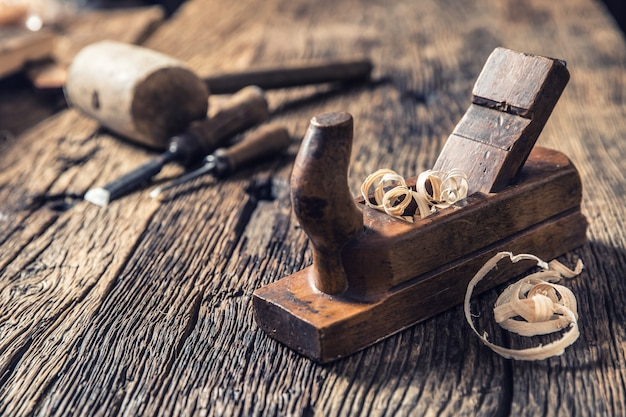Ancienne raboteuse et autres outils de menuisier vintage dans un atelier de menuiserie.