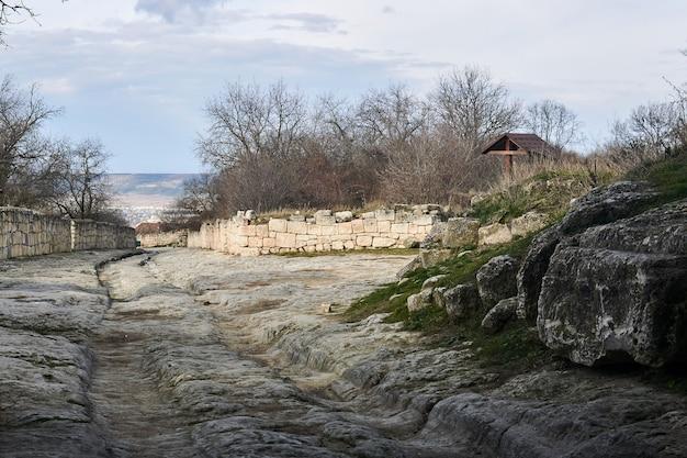 Ancienne route avec des ornières de chariots en pierre aux ruines de la ville médiévale de chufut-kale, crimée