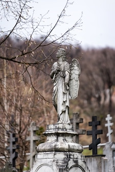 Ancienne sculpture en pierre tombale d'un ange avec bras et ailes cassées sur le cimetière