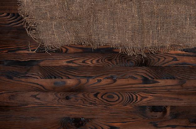 Ancienne serviette en toile de jute sur fond en bois marron, vue de dessus