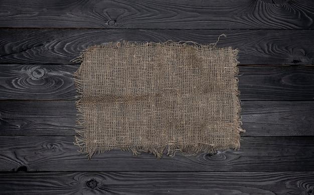 Ancienne serviette en toile de jute sur fond en bois noir, vue de dessus