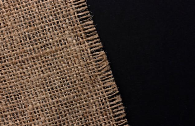 Ancienne serviette en toile de jute sur fond noir, vue de dessus