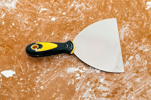 Ancienne spatule utilisée et sale sur le sol, effectuant des réparations dans le bâtiment