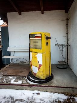 Ancienne station-service abandonnée avec pompe jaune