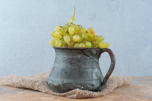 Une ancienne tasse pleine de raisins sucrés sur marbre