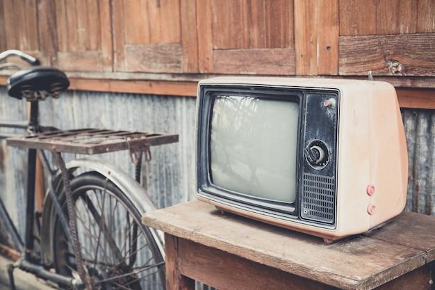 Ancienne télévision et vieux vélo décoratif au mur en bois.