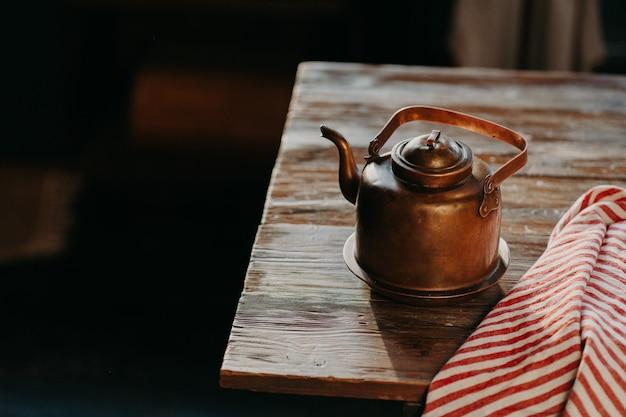 Ancienne théière en métal cuivre sur table en bois dans une pièce sombre. serviette rayée rouge à proximité. bouilloire antique pour faire du thé ou du café. équipement de cuisine