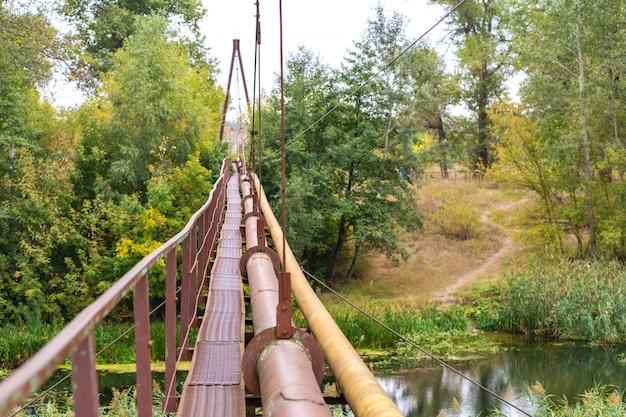 Une ancienne traversée de rivière rouillée étroite, avec un tuyau d'eau et de gaz. communications dans le village.