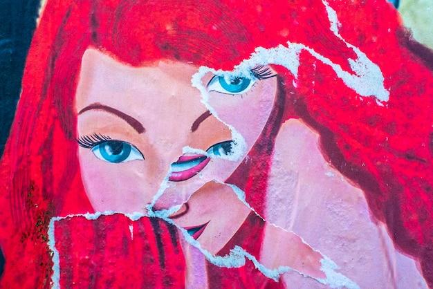 Anciennes affiches publicitaires brisées, visage de fille avec plusieurs yeux comme une croix
