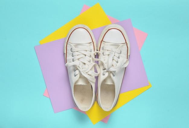 Anciennes baskets rétro à lacets blancs sur fond pastel coloré. le minimalisme. vue de dessus