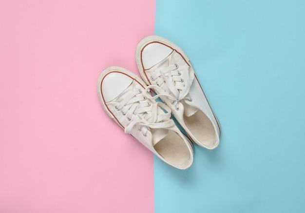 Anciennes baskets rétro à lacets blancs sur fond pastel rose bleu. le minimalisme. vue de dessus