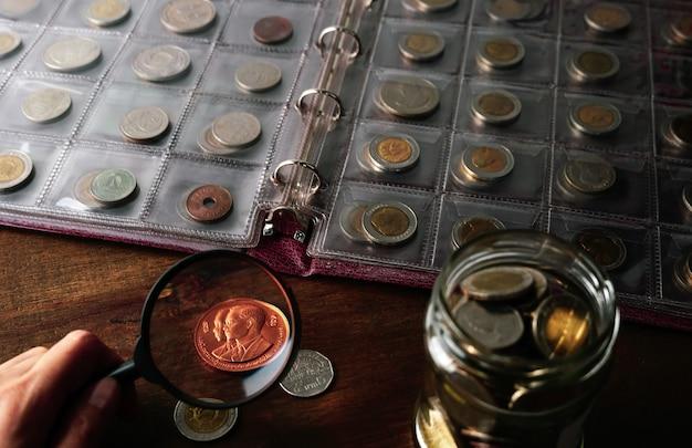 Anciennes pièces de collection sur une table en bois fond sombre bannière numismatique pièces dans l'album