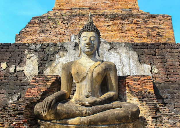 Anciennes statues de bouddha sur mur de briques orange