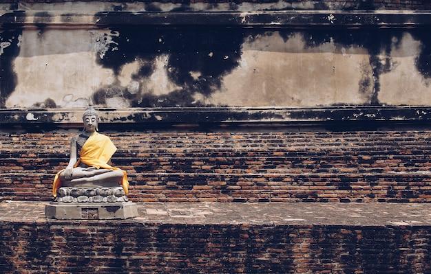 Anciennes statues de bouddha placées sur des murs de briques dans les temples thaïlandais.