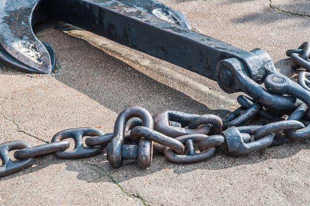 Ancre de navire en métal lourd avec chaîne sur asphalte gris. fermer.