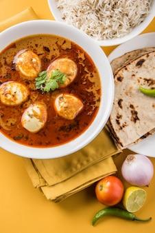 Anda curry ou egg masala sauce, cuisine indienne épicée ou recette, servie avec du riz jeera, roti ou naan, mise au point sélective. sur un dessus de table coloré ou en bois