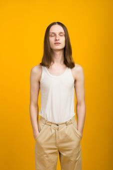 Androgyne beau jeune homme. essais de modèle dans le mur jaune