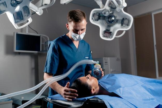 Anesthésiste faisant l'anesthésie d'ingalation pour le patient. le docteur met un masque sur le patient avant de commencer l'opération