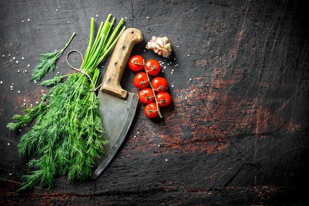 Aneth frais avec couteau, tomates et gousses d'ail sur table rustique sombre.