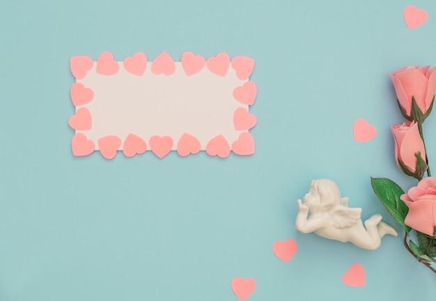 Ange blanc, feuille vierge avec cadre coeurs roses et roses sur bleu