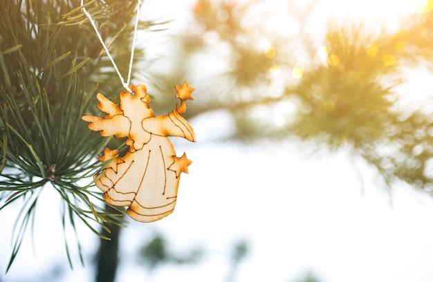 Ange en bois fait à la main accroché au pin de noël. photo naturelle dans la forêt gelée. carte postale d'ornements de joyeuses fêtes. temps de neige.