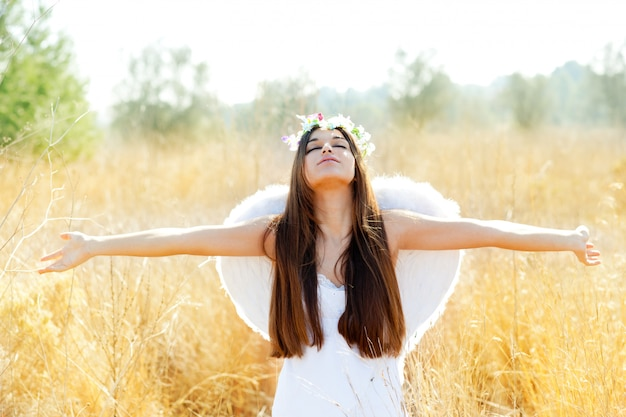Ange fille dans un champ doré avec des ailes de plumes blanches