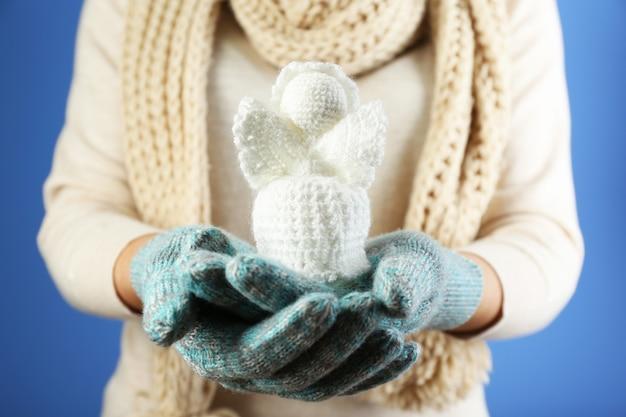 Ange de noël tricoté dans une main féminine sur une surface de couleur