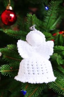 Anges de noël tricotés et autres décorations sur fond d'arbre de noël, gros plan