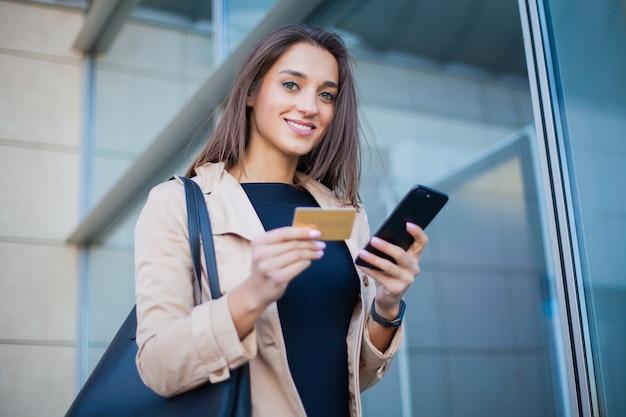 Angle bas de la fille heureuse debout dans le hall de l'aéroport. il utilise une carte de crédit et un téléphone portable gold pour payer