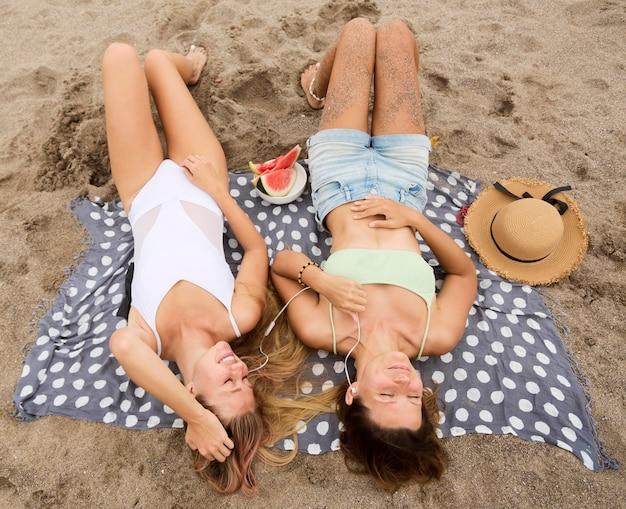Angle élevé des amies se détendre à la plage