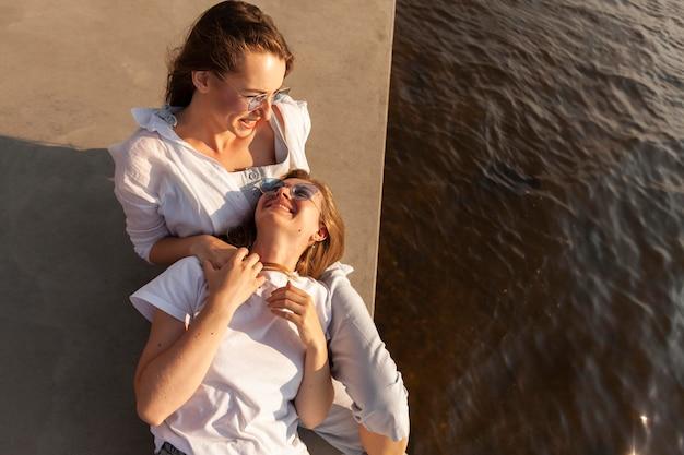 Angle élevé d'amis féminins smiley s'amusant au bord du lac avec espace copie