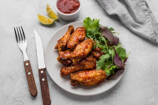 Angle élevé d'assiette avec poulet frit et salade avec sauce et couverts