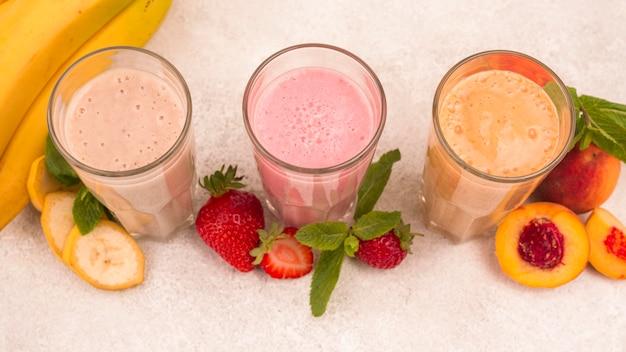 Angle élevé d'assortiment de laits frappés aux fruits dans des verres