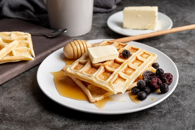 Angle élevé de beurre et de miel sur des gaufres