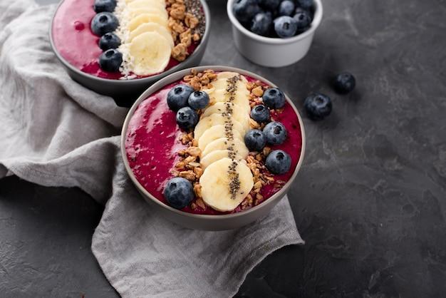 Angle élevé de bols avec desserts pour le petit-déjeuner et assortiment de fruits et céréales