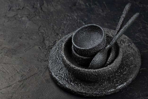 Angle élevé de bols noirs et cuillères sur ardoise