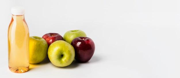 Angle élevé de bouteille de jus de fruits avec des pommes