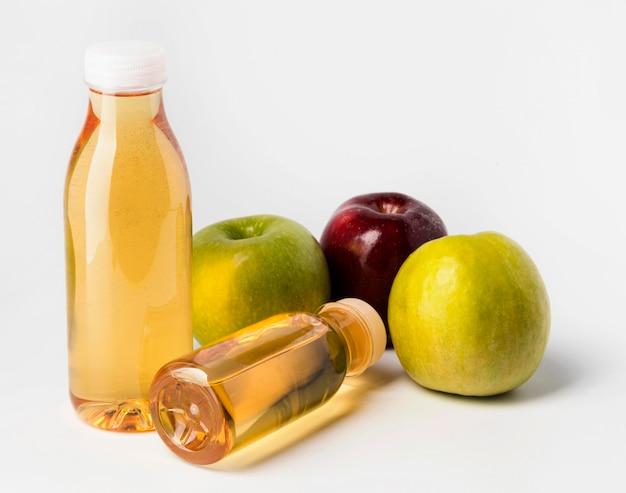 Angle élevé de bouteilles de jus de fruits avec des pommes