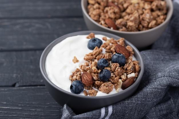 Angle élevé de céréales de petit déjeuner avec des bleuets et du yaourt