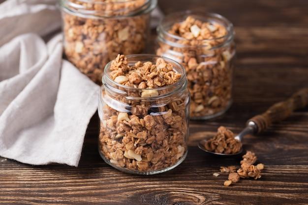 Angle élevé de céréales pour petit déjeuner dans des bocaux avec bientôt