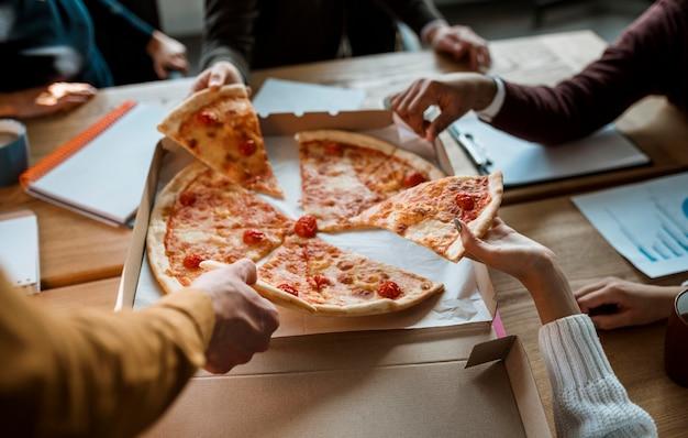 Angle élevé de collègues ayant une pizza lors d'une pause de réunion de bureau
