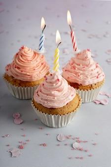 Angle élevé de cupcakes d'anniversaire avec glaçage et bougies allumées