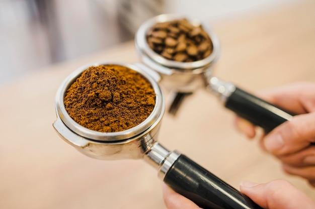 Angle élevé de deux tasses de machine à café tenues par le barista